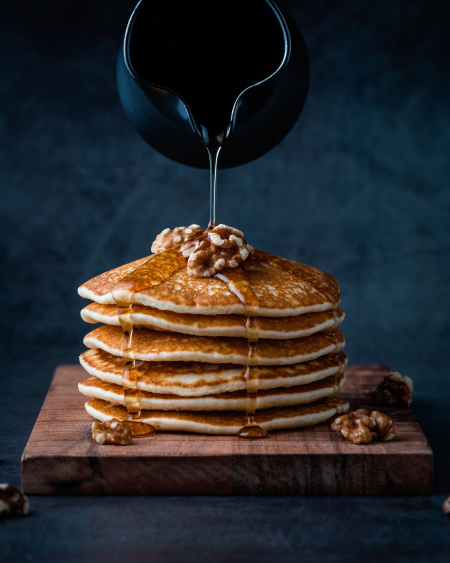 Foodiesfeed.com_pouring-honey-on-pancakes-with-walnuts